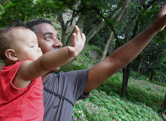 Marcio, a father in Brazil, holds his son as they both reach for the sky