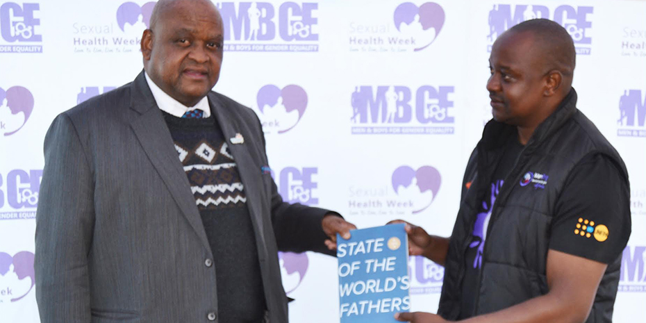 Botswana Assistant Minister from the Office of the President, Phillip Makgalemele, receives a copy of State of the World's Fathers at the Shoshong launch.